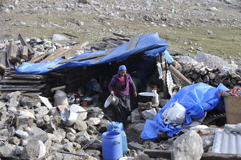 In this photograph taken on April 7, 2016, Nepalese villagers prepare to cook food in a temporary shelter in the village of Langtang. Langtang in Nepal is now little more than a graveyard. The once tranquil mountain village was obliterated last April when a massive earthquake shattered a glacier, raining tonnes of ice, snow and rock down into the valley below, where hundreds of bodies still lie buried. / AFP PHOTO / PRAKASH MATHEMA / TO GO WITH AFP STORY NEPAL-QUAKE-ANNIVERSARY, FEATURE BY AMMU KANNAMPILLY