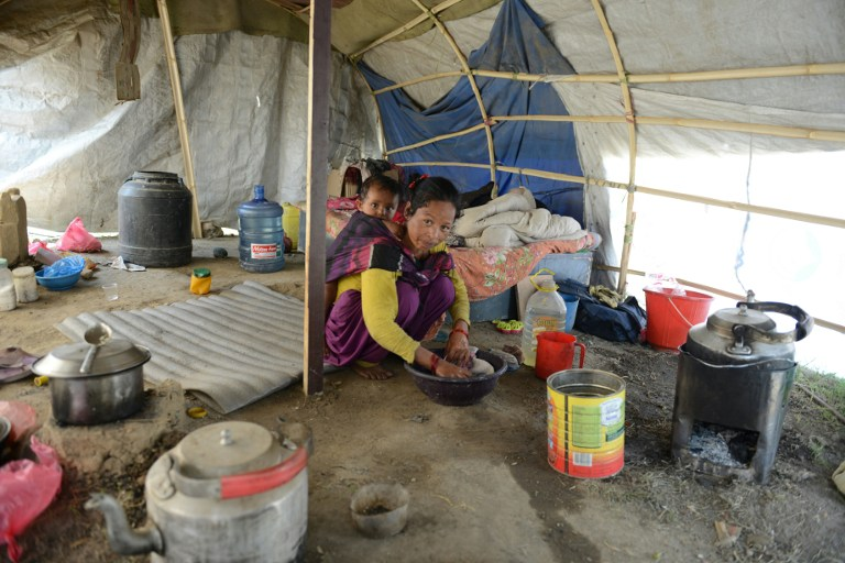 In this photograph taken on April 21, 2016, Nepalese earthquake survivor Menuka Rokaya cares for her child as she speaks with AFP in Ramechhap on the outskirts of Kathmandu. A year after an earthquake flattened her home in Nepal, Menuka Rokaya still lives in a tent with her husband and nine-month-old baby as they await even a sliver of a USD 4 billion aid fund. / AFP PHOTO / PRAKASH MATHEMA