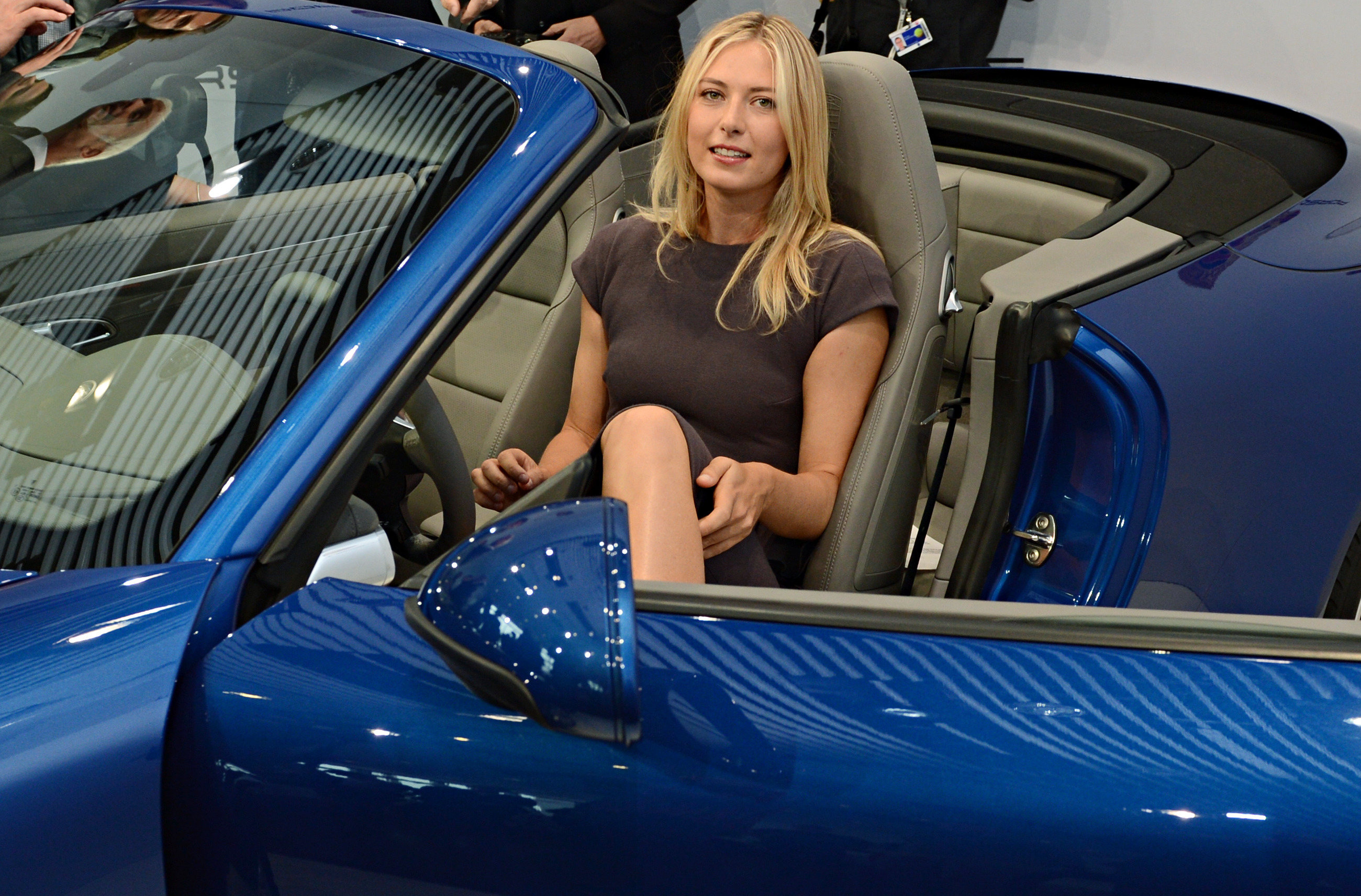 Russian tennis player Maria Sharapova poses inside a Porsche 911 in Stuttgart, southern Germany, on April 22, 2013. Sharapova will be the first global ambassador for German car manufacturer Porsche. AFP PHOTO / FRANZISKA KRAUFMANN GERMANY OUT / AFP / DPA / FRANZISKA KRAUFMANN