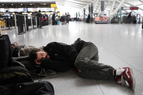 NEW YORK, NY - JANUARY 27: Bruno Rocha sleeps on the floor of John F. Kennedy Airport after having his flight to Brazil delayed due to a winter storm on January 27, 2011 in New York City. Rocha had been on vacation in the United States with two friends.  New York City, still reeling after the Christmas blizzard, closed public schools and limited public transportation following another heavy snowstorm. (Photo by Andrew Burton/Getty Images)