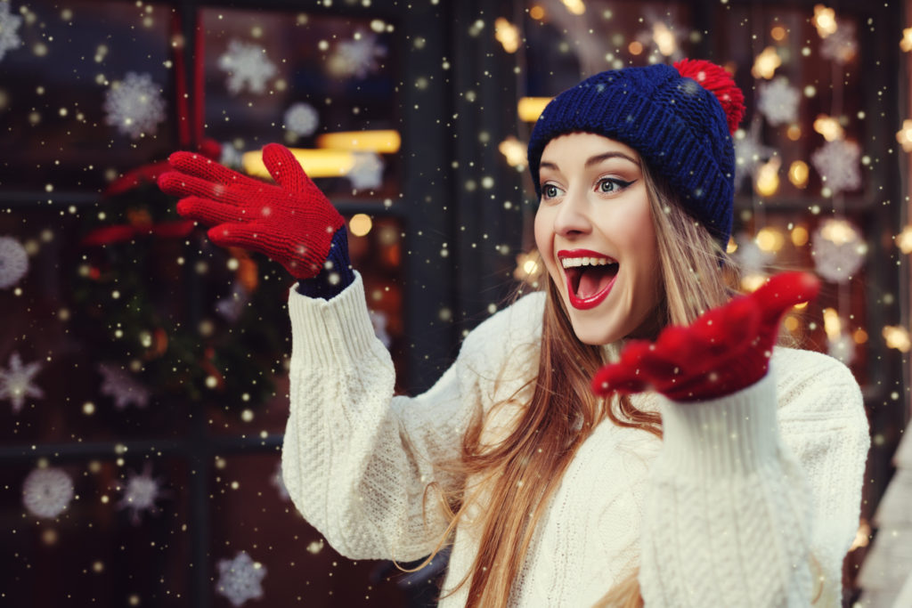 Street portrait of young beautiful woman acting thrilled, wearing stylish knitted clothes. Model expressing joy and excitement with hands and face. Festive garland lights. Snowfall effect. Close up.