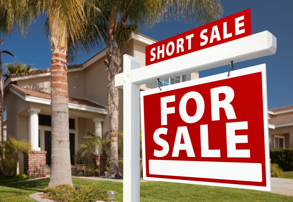 short sale sign in front of beautiful home