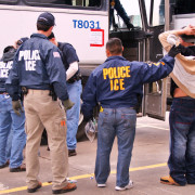 U.S. Immigration and Customs Enforcement Agents transporting suspects after a raid