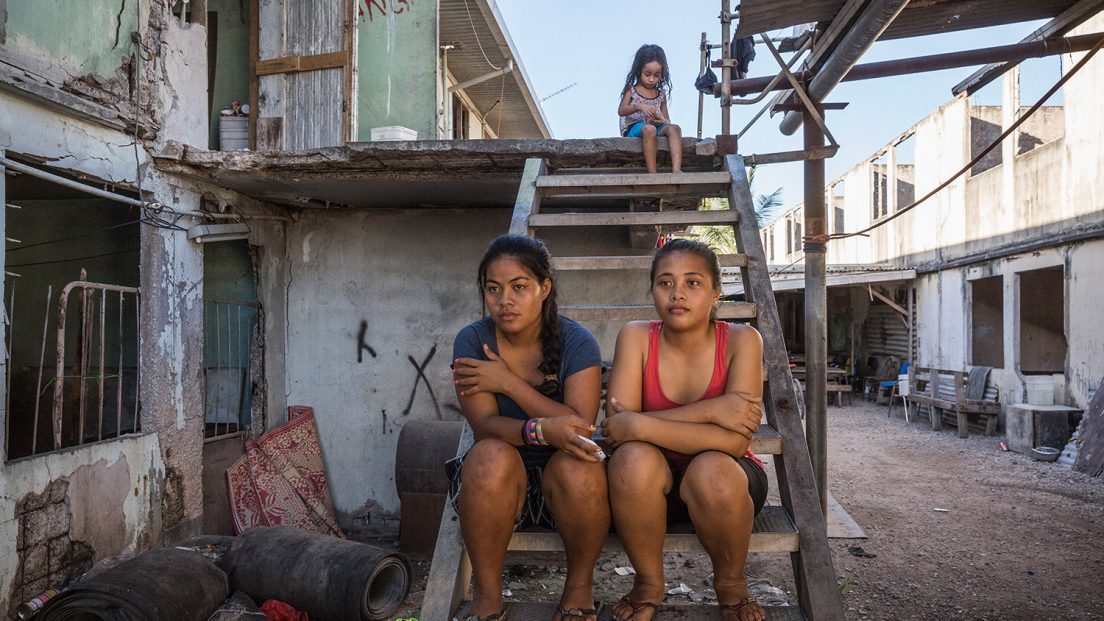 Tewira (19, left) and Lusia (14, right) sit on the stairs in front of their family house in the Location Block. Their parents came to Nauru from Tarawa, Kiribati looking for work and a better future for their children. Soon after Nauru started having economical problems in the early 2000s, they and many other people lost their jobs and became squatters in the Location Block Area. Location Block was a residential area for foreign miners who came to Nauru to work on the phosphite mine. After the closure of the mine in the early 2000s most of the miners left Nauru and the Location Block became a squatters settlement, mostly populated by locals. Image by Vlad Sokhin