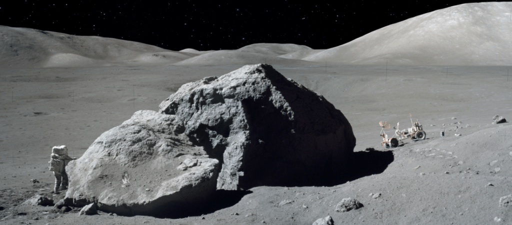 NASA scientist-astronaut Harrison Schmitt is standing next to a huge, split lunar boulder during the third Apollo 17 mission. The Lunar Roving Vehicle, which transported Schmitt from the Lunar Module, is seen in the background.