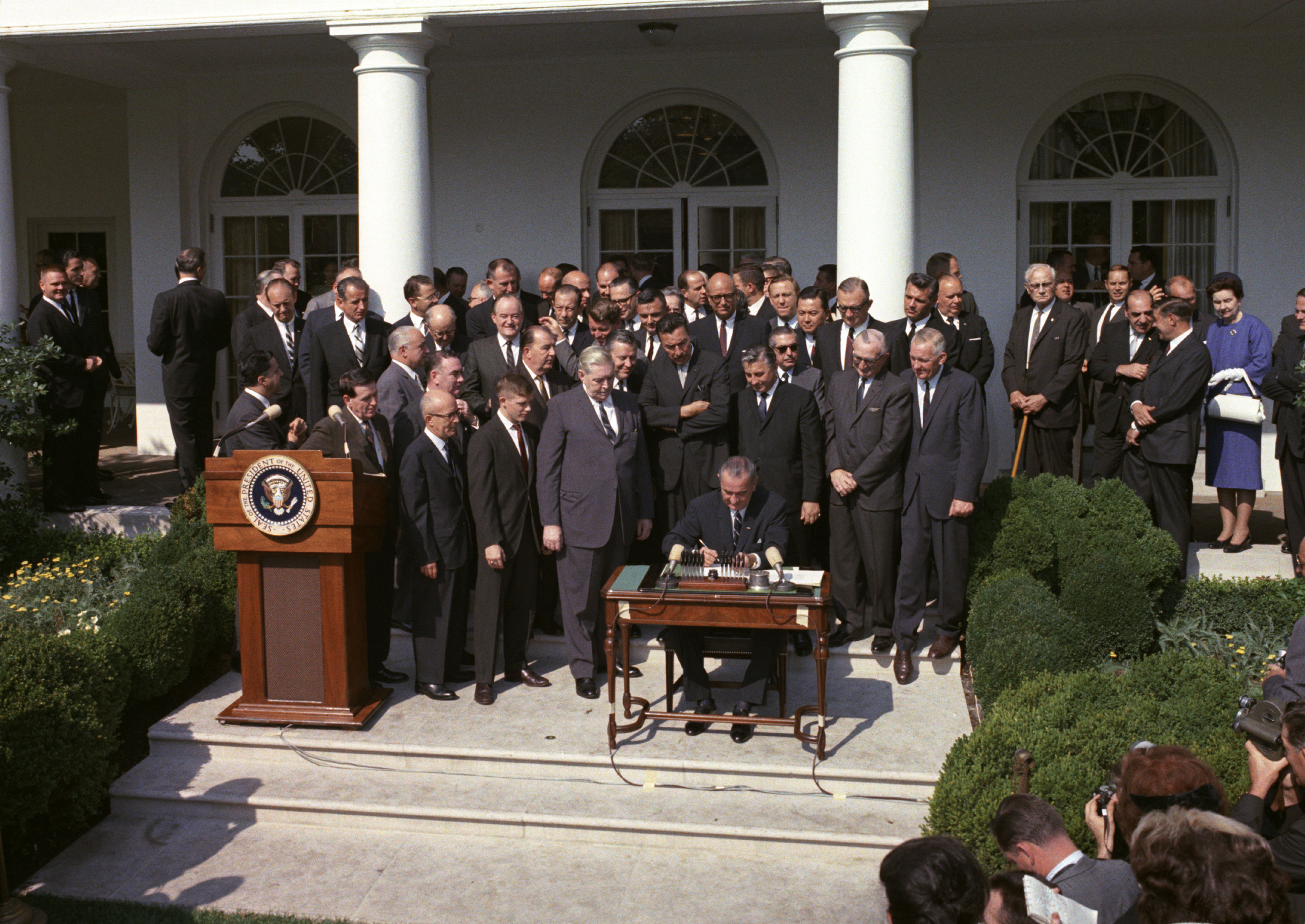 President Lyndon B. Johnson signs the Poverty Bill