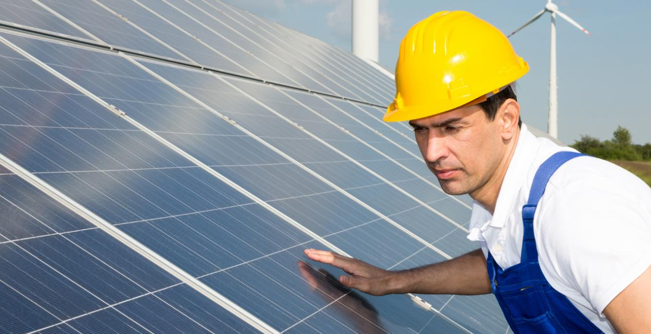A worker in a hard hat inspects a PV solar installation.