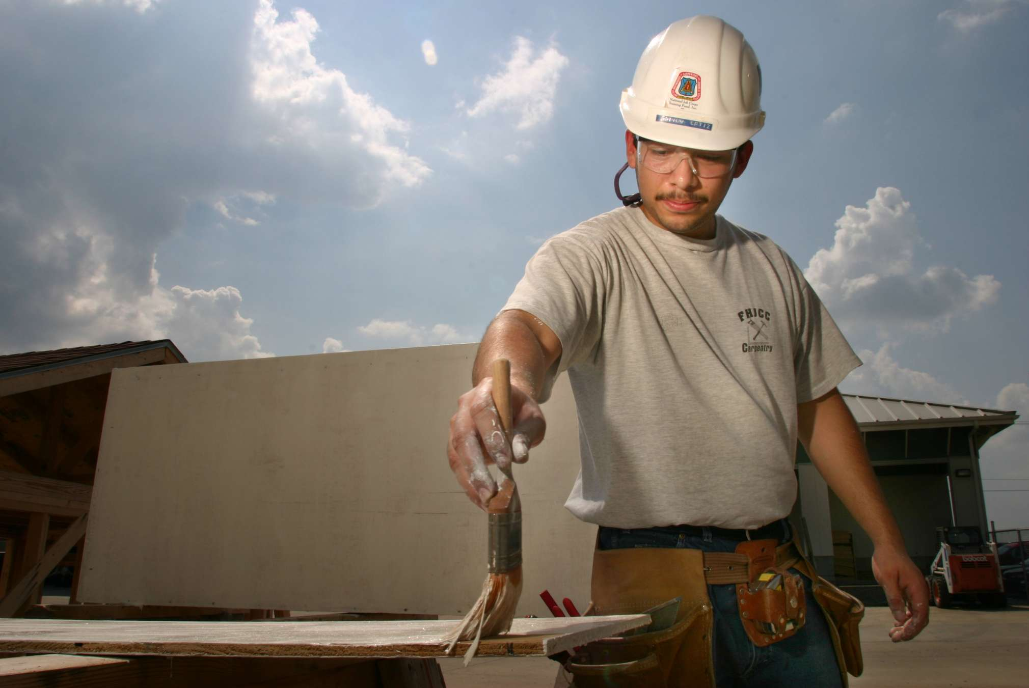 young man in a hard hat painting a board