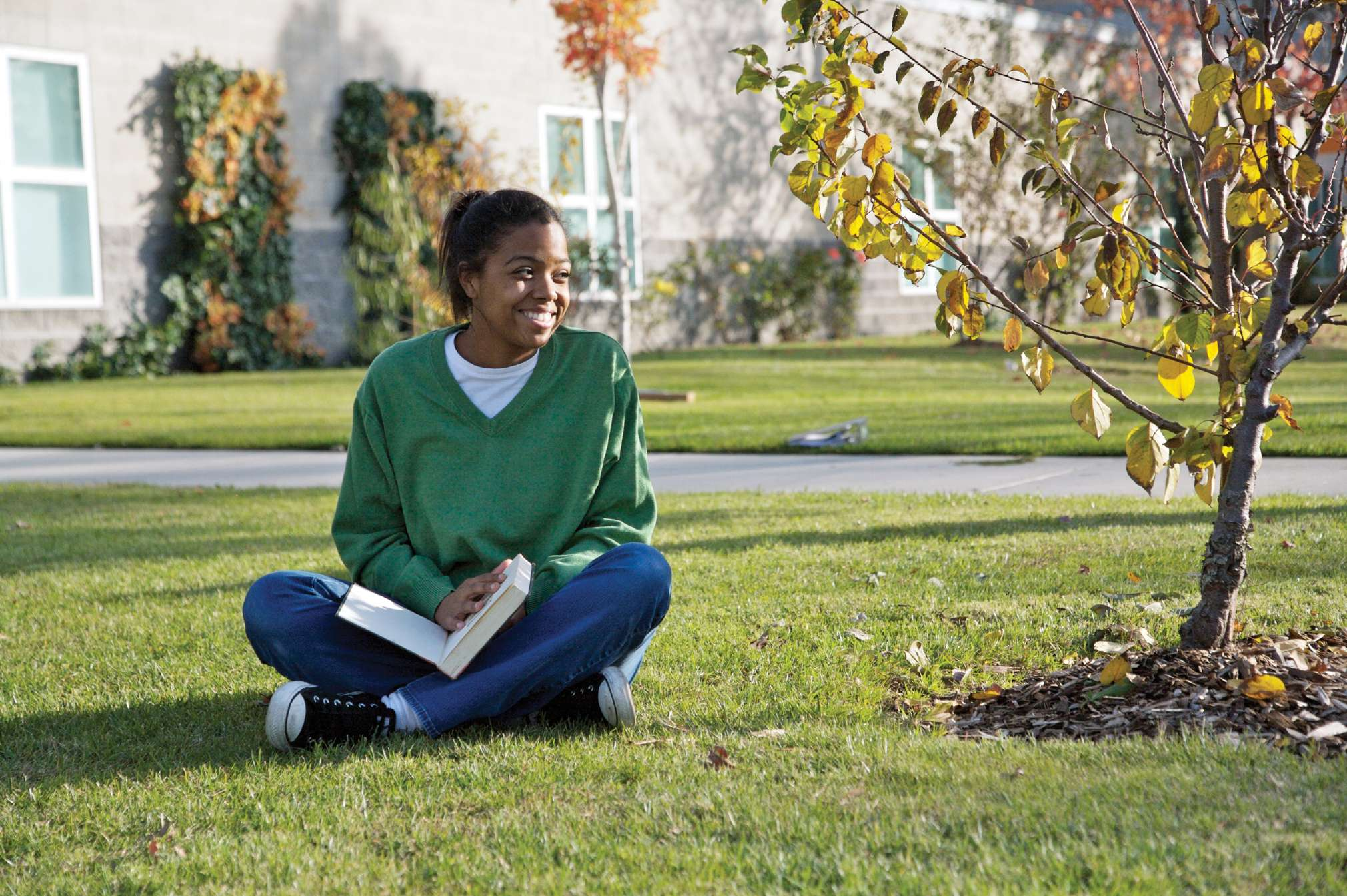 Young woman sitting on the grass reading a book