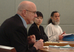 John Marvin, Jr. (right) and Grace Lee from the Public Defender's office (center) both listen as District Attorney Dave Brower (left foreground) makes a point during the first part of a competency hearing on Friday. Photo by Matt Miller-KTOO News