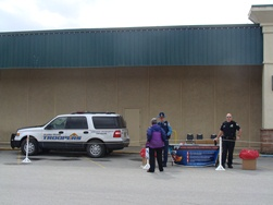 Trooper Chris Umbs and JPD Officer Thomas Penrose man the National Prescription Drug Take-Back Day table at Nugget Mall Saturday. (Photo by Casey Kelly/KTOO)