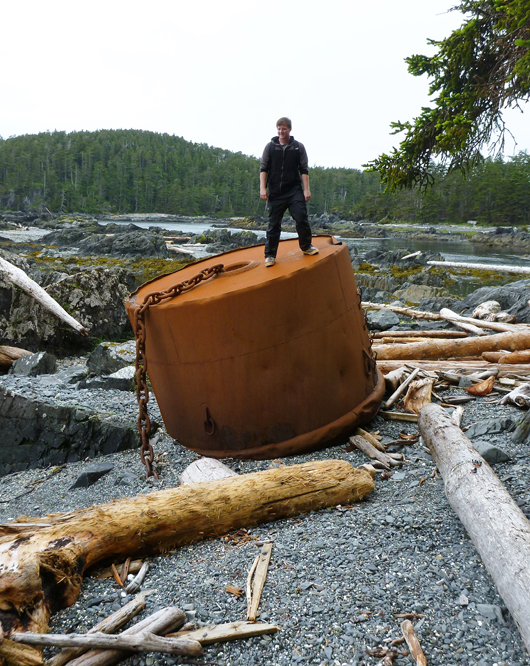 University of Alaska student Derek Chamberlin stands atop a large ship's mooring buoy which must have broken off it's chain anchor. The mooring buoy was found by NOAA marine debris scientists at Whale Bay, North Cape on Baranof Island during a recent marine debris survey of Southeast Alaska shores.