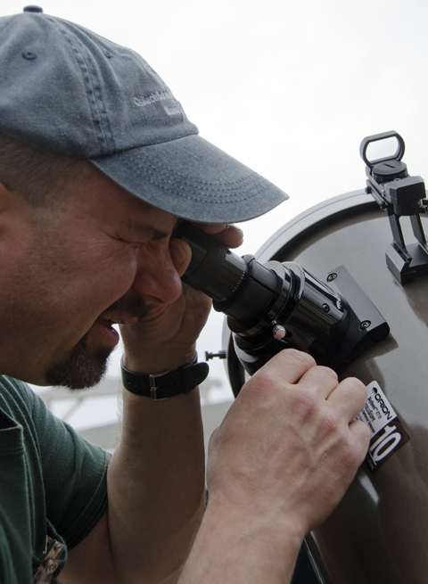 Clark Branch adjusts the eyepiece on a 10 inch Newtonian Reflector Telescope.