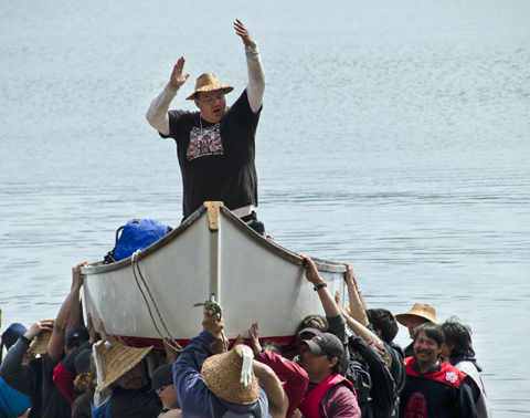 The group leader cheers as people carry the canoe ashore.