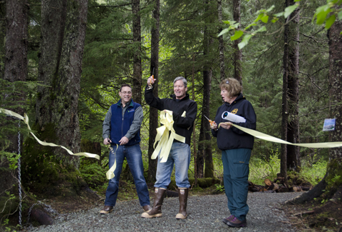 Brent Fischer, director of Juneau Parks and Recreation, Jack Kreinheder, Trail Mix President, and Marti Marshall, U.S. Forest Service District Ranger cut the ribbon to the Under Thunder trail in Mendenhall Valley.