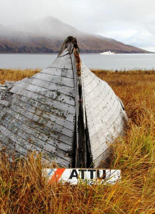An old boat of bygone days on Attu Island.  In the background, the Cutter Sherman is anchored in Massacre Bay. Photo by Capt. Joe Hester.