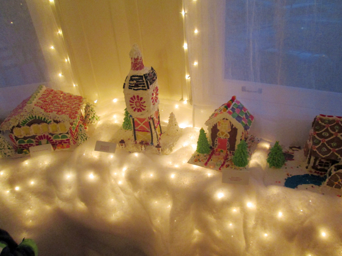 The candy house display lights up the window.