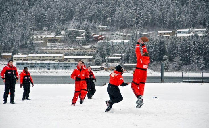 Taking advantage of the perfect snow covered lot, a group from the Coast Guard base take a break for a little football.