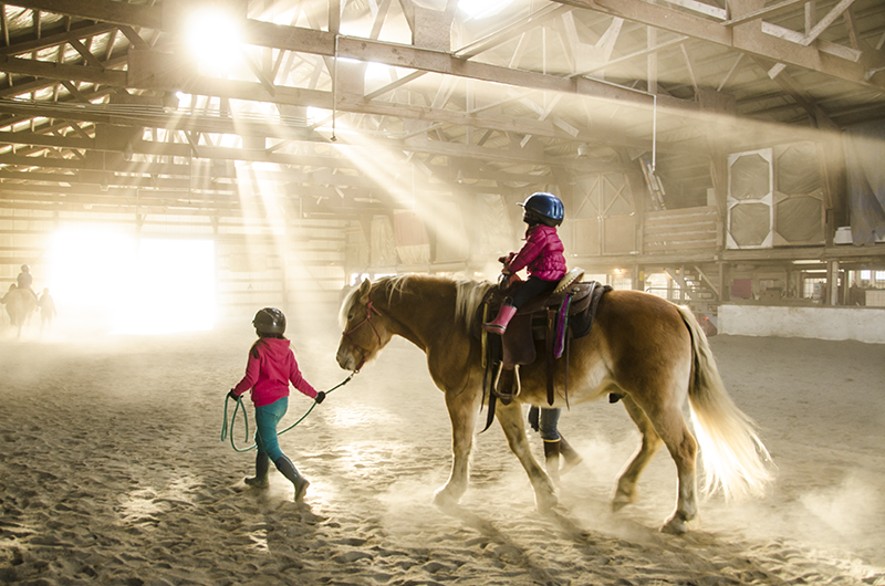 A new 4-H equestrian club in Juneau links riders at Fairweather stables to the Southeast 4-H community.The group hosted their first pony ride in October. Sunlight streams into the dusty barn as Higgins carries another rider around the arena.