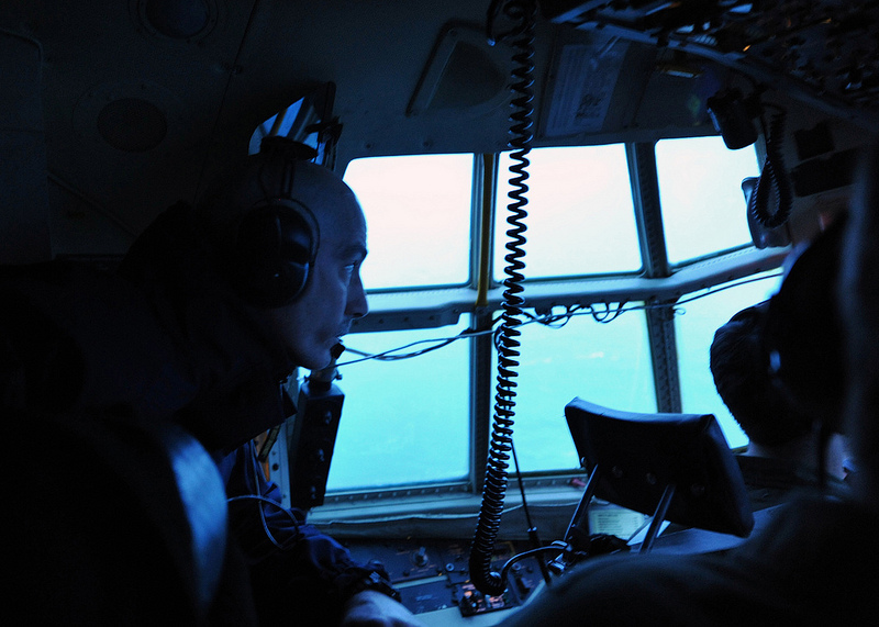 Rear Adm. Thomas Ostebo, commander, 17th Coast Guard District, and D17 Incident Management Team commander, peers out the window of a Coast Guard Air Station Kodiak, Alaska, HC-130 Hercules airplane as the crew flies over the grounded conical drilling unit Kulluk on the southeast side of Sitkalidak Island Jan. 1, 2013. Ostebo, the first senior federal official to visit the site, flew aboard two Coast Guard aircraft to ensure he had full situational awareness of the incident, which occurred in his area of responsibility. U.S. Coast Guard photo by Petty Officer 3rd Class Jonathan Klingenberg.