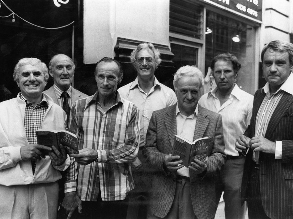 The Great Train Robbers, left to right: Buster Edwards, Tom Wisbey, Jim White, Bruce Reynolds, Roger Cordrey, Charlie Wilson and Jim Hussey, with copies of their book 'The Train Robbers' in 1979. Michael Fresco/Getty Images