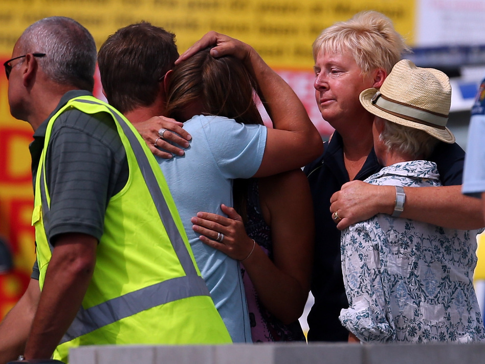 People grieve outside New Zealand's Muriwai Surf Lifesaving Club after the fatal shark attack at Muriwai Beach on Wednesday. Phil Walter/Getty Images