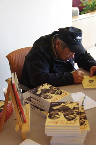 Attu survivor and author Nick Golodoff signs copies of Attu Boy. (Photo by Stephanie Joyce/KUCB)