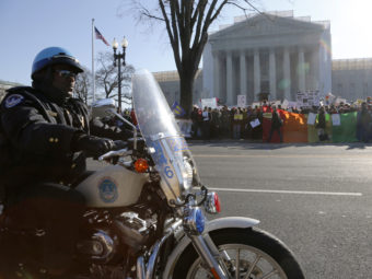 A Washington D.C. motorcycle police officer kept watch on demonstrators outside the Supreme Court Tuesday morning. Jonathan Ernst /Reuters /Landov