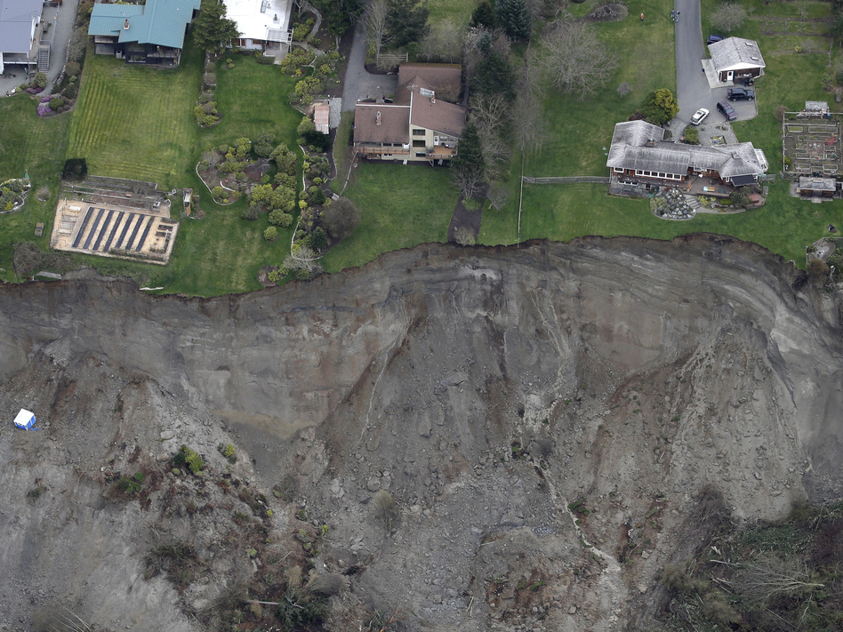 Houses sit near the edge of a landslide on Whidbey Island on Wednesday. Ted S. Warren/Associated Press