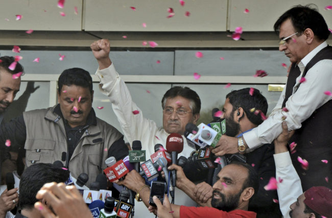Former Pakistani President Pervez Musharraf greets supporters upon his arrival at Karachi airport in Pakistan on Sunday. S.I. Ali/AP