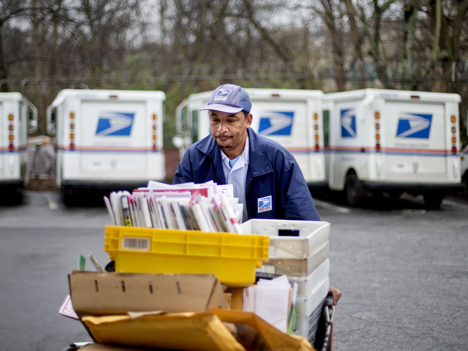 Veteran USPS letter carrier Michael McDonald gathers mail to load into his truck before making his delivery run in the East Atlanta neighborhood on Thursday, Feb. 7, 2013, in Atlanta. David Goldman/AP