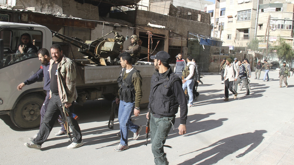 Rebels from the Free Syrian Army walk on a street in Damascus in this picture provided by Shaam News Network and taken March 23.