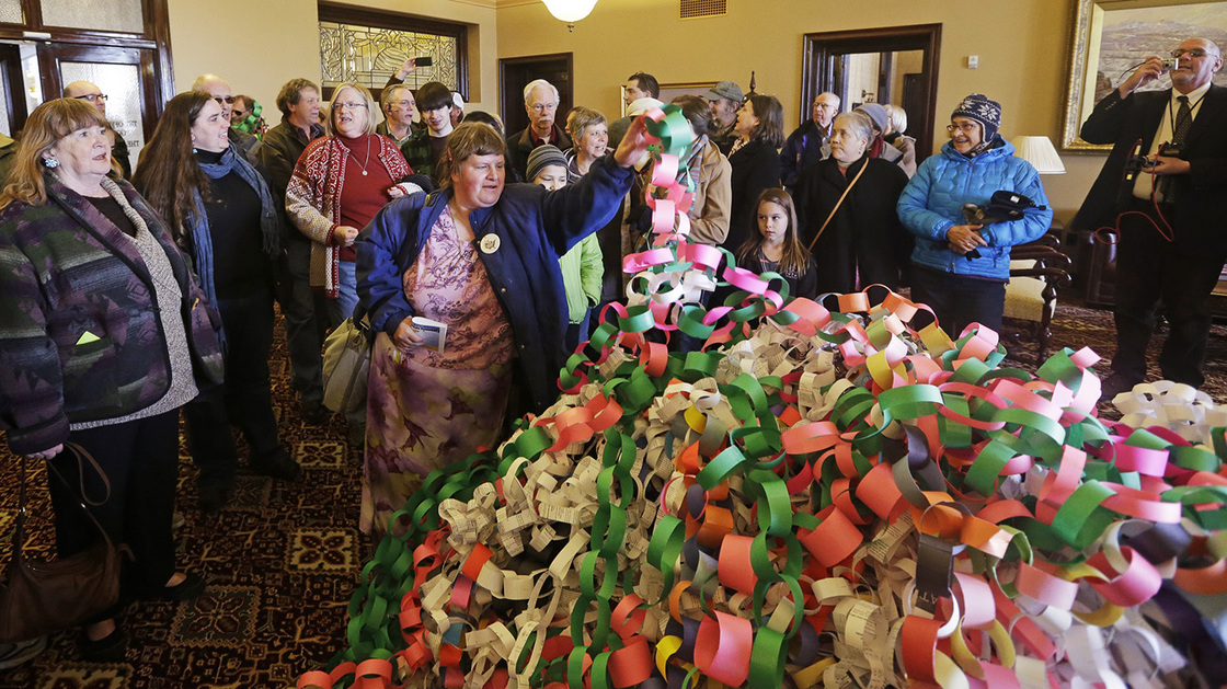 Outside the office of Utah Gov. Herbert Friday, Betsy Ogden lays paper chains on a pile symbolizing uninsured state residents who would be covered by a Medicaid expansion. Rick Bowmer/AP