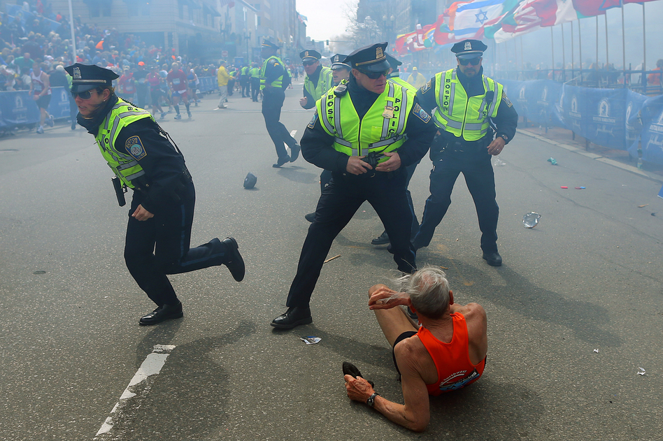 Police officers with their guns drawn hear a second explosion down the street near the finish line of the Boston Marathon. The first explosion knocked down a runner at the finish line. John Tlumacki/Boston Globe via Getty Images