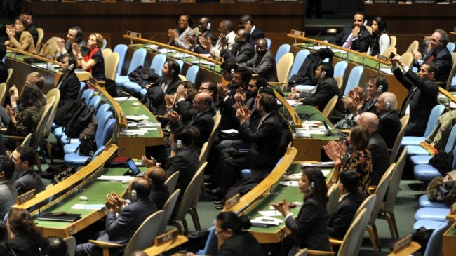 Delegates to the United Nations General Assembly applaud the passage of the first U.N. treaty regulating the international arms trade on Tuesday. Timothy A. Clary /AFP/Getty Images