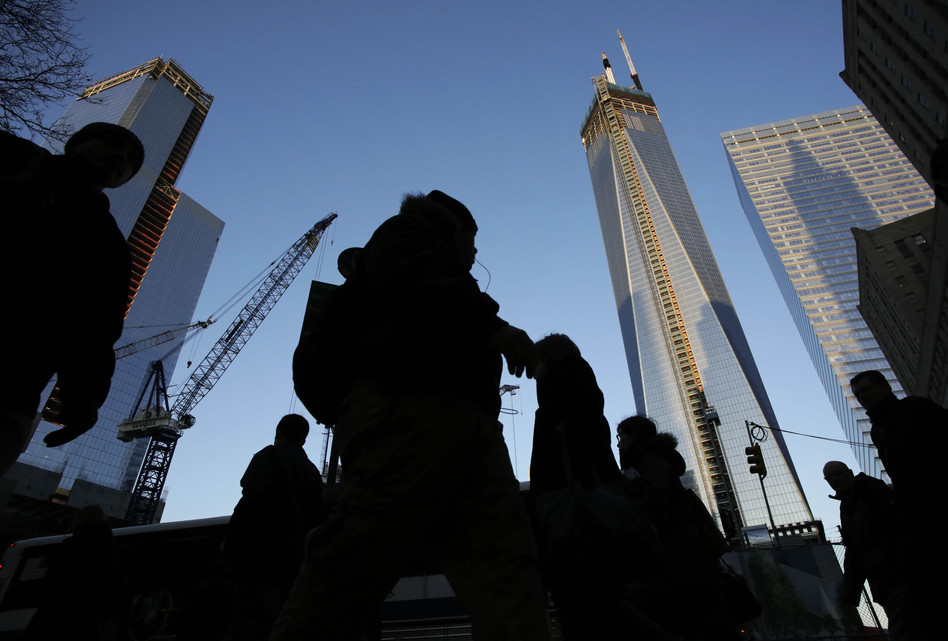 People pass the World Trade Center construction site in New York. Debris from the fallen towers will be sifted for victims' remains beginning Monday. Mark Lennihan/AP