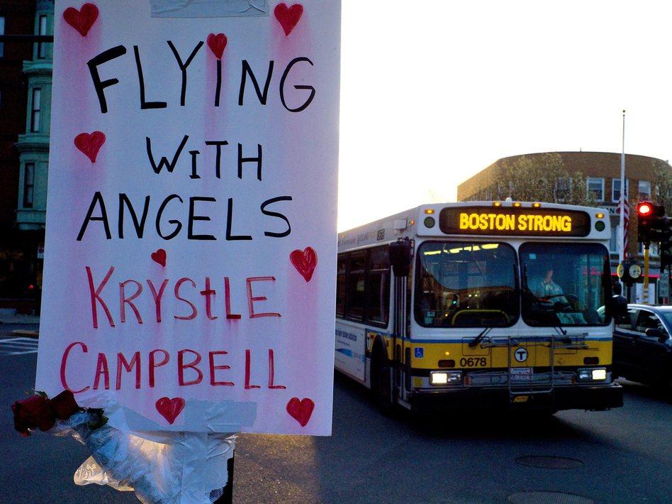 "A sign reading ""Flying With Angels Krystle Campbell,"" is seen Monday as a passing MBTA bus with ""Boston Strong"" displayed on its message board drives through Medford, Mass. A funeral service for Campbell, one of the three people killed in the marathon bombings, was to be held later in the day. C.J. Gunther /EPA /LANDOV"