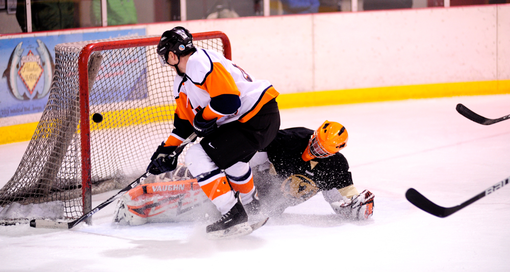 Alec Venechuk lifts a backhand shot past a sprawling Jerry Nankervis in goal during a Tier A playoff contest.