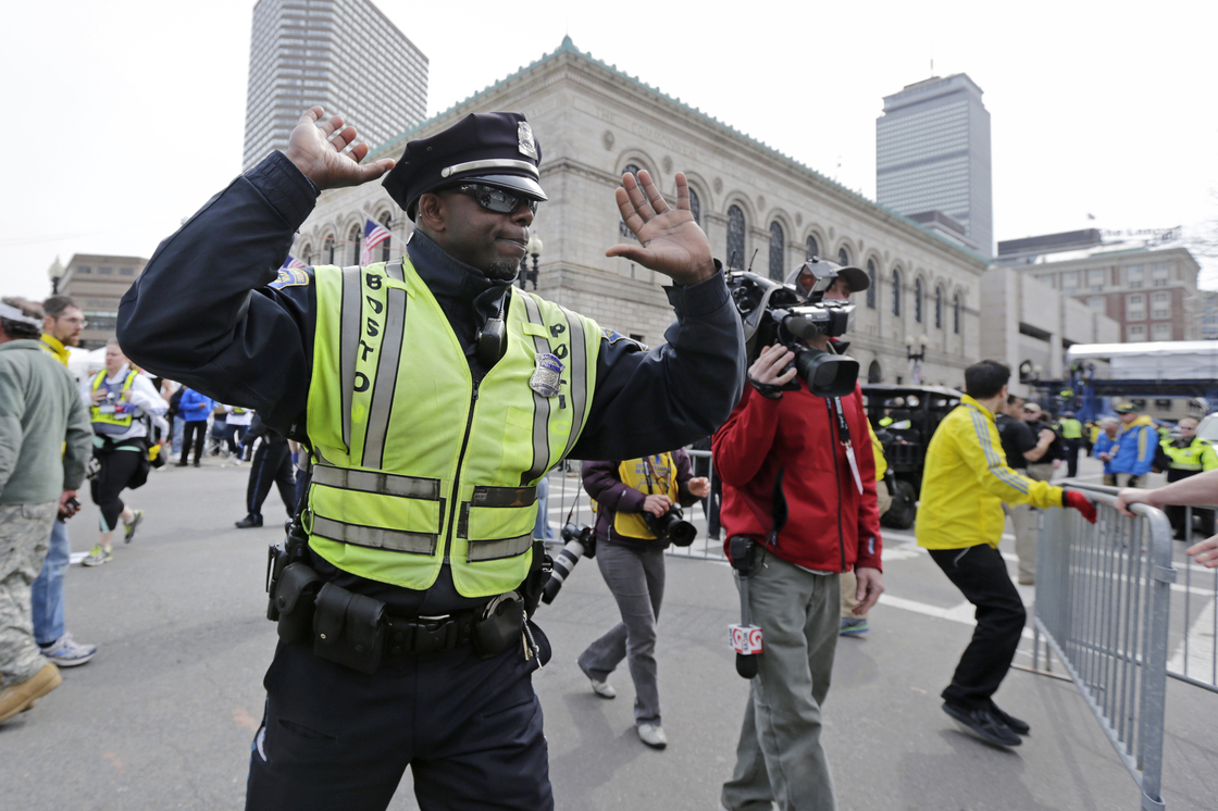 A Boston police officer clears Boylston Street following the explosions. Charles Krupa/AP