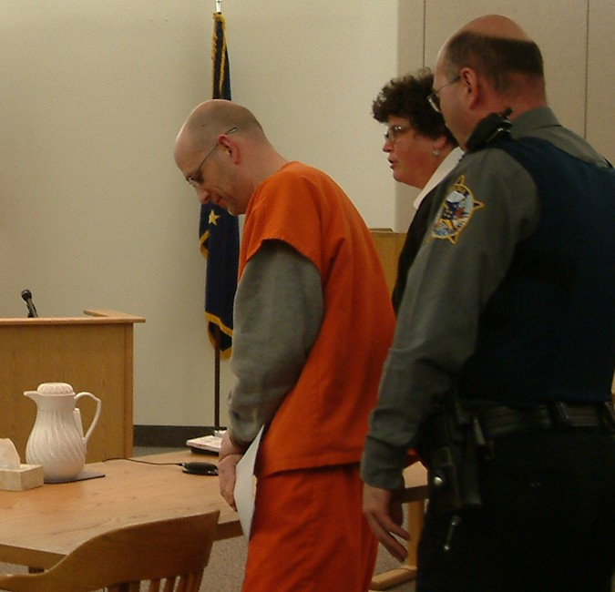 Troy Wilson prepares to leave the courtroom after his change of plea hearing on Wednesday. His attorney Julie Willoughby is partially obscured behind Wilson's Judicial Services escort. Photo by Matt Miller/KTOO News