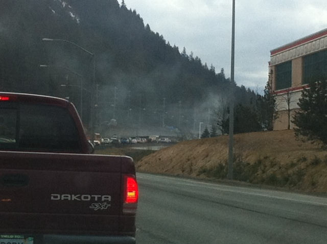 Smoke from the vehicle fire rises over the line of cars on Egan.