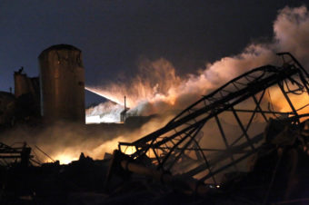 Smoke rises as water is sprayed at the burning remains of the plant.