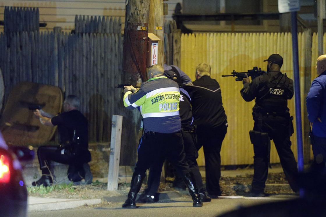 Police officers search a street near Watertown, Mass. Photo by Matt Rourke/AP