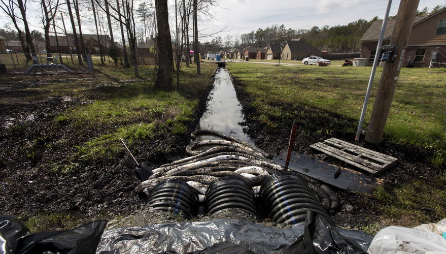 Spilled crude oil is seen in a drainage ditch near evacuated homes near Starlite Road in Mayflower, Ark., on March 31. An Exxon Mobil pipeline carrying Canadian crude oil was shut off after a ruptured on March 29, causing an evacuation of 22 homes. Jacob Slaton/Reuters/Landov