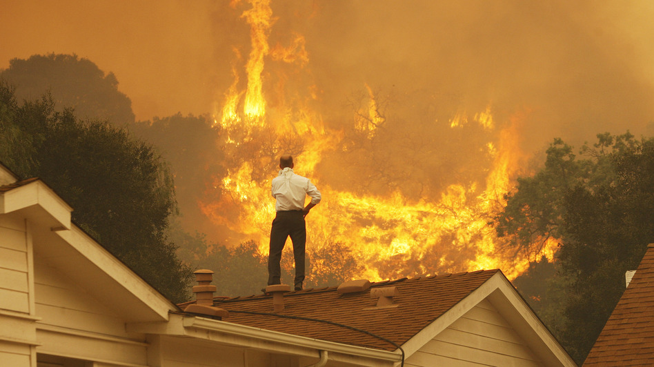 Standing on a rooftop, a man looks at the Springs fire's approaching flames in California Friday. The wildfire, reportedly, 20 percent contained, might be weakened by high humidity and cooler temperatures Saturday. David McNew/Getty Images
