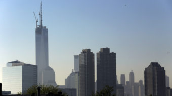 One World Trade Center stands at its full height of 1,776 feet Friday, after a crane lifted its spire into place. The New York City skyline is seen here from the Heights neighborhood of Jersey City, N.J. Julio Cortez/AP