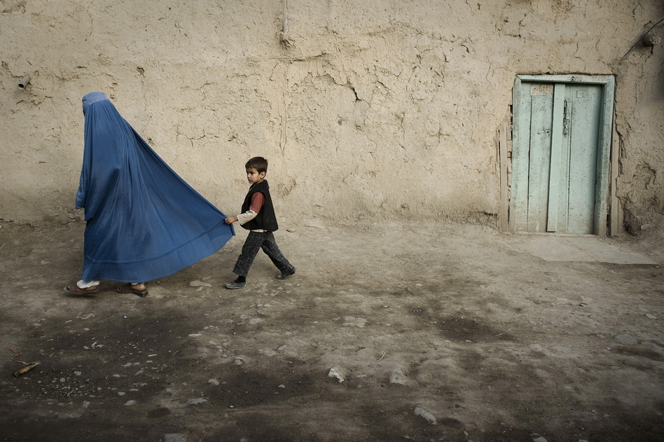 A boy holds the burqa of his mother as they walk down a street in the old city of Kabul on November 1, 2009. Nicolas Asfouri/AFP/Getty Images