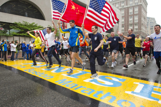 "Runners holding American flags and a Chinese flag cross the finish line after completing the final mile of the Boston Marathon course during ""#onerun"" in Boston, Massachusetts on Saturday. Dominick Reuter /Reuters /Landov"