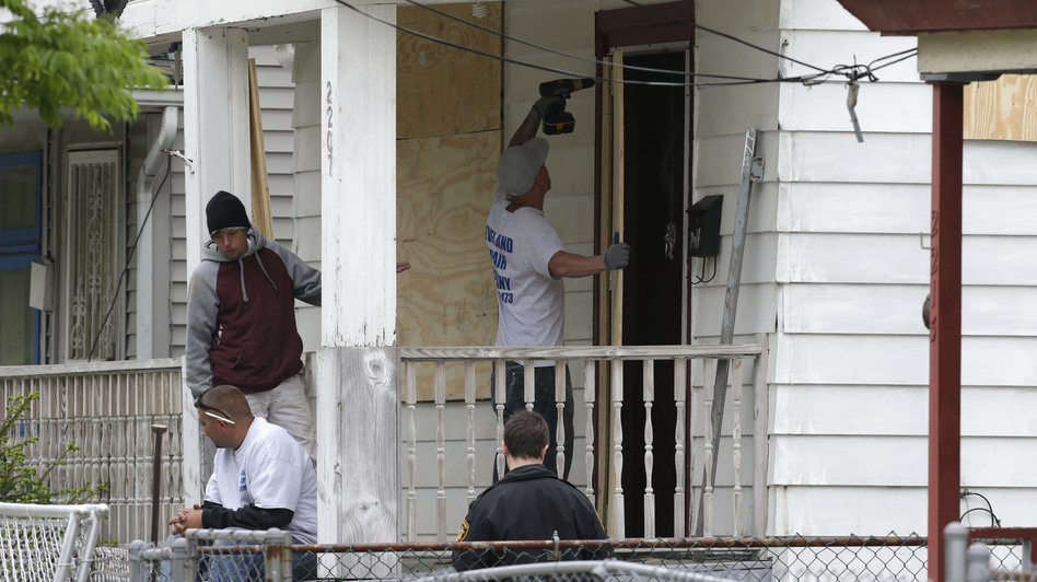 Workers board up the house where three women were held in Cleveland Saturday. Suspect Ariel Castro, who allegedly held three women captive for nearly a decade, is charged with rape and kidnapping. Sunday, the women asked for privacy and time to connect with their families. Tony Dejak/AP