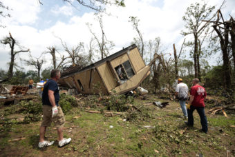 Volunteers help clean out Jean McAdams' mobile home after it was overturned by a tornado today near Shawnee, Oklahoma. Brett Deering/Getty Images